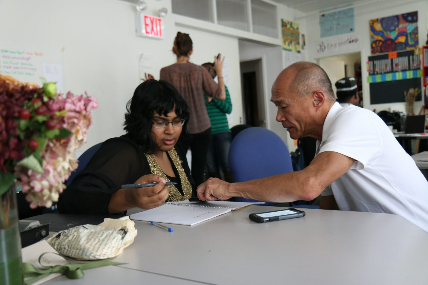 a woman and man sitting at a table with a mobile phone and a notebook